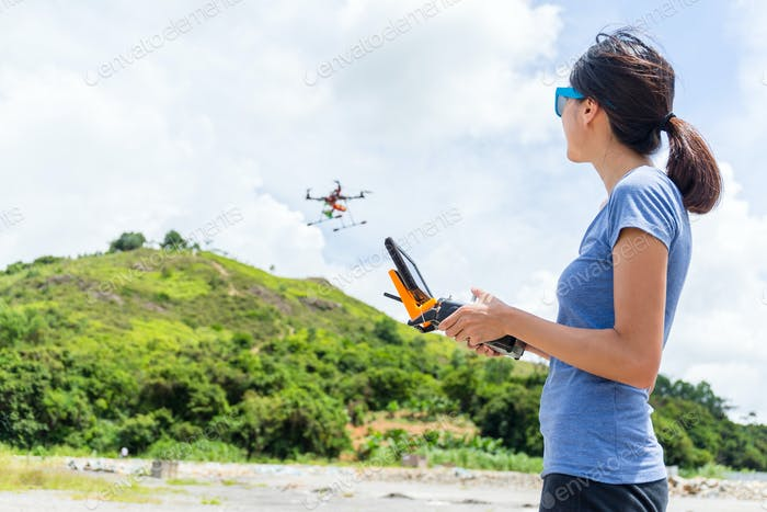 Young Woman control flying drone