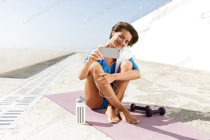 Woman in blue swimsuit and earphones on purple yoga mat and taking selfie on cellphone