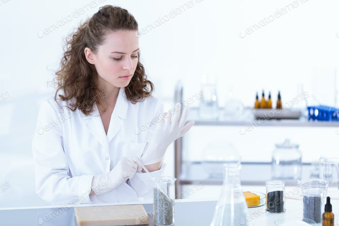 Chemist putting on glove