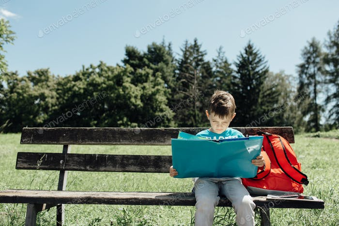 Schoolboy sitting alone on a bench and reading a book