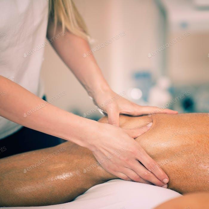 Leg massage. Physical therapyst massaging leg of young male athe