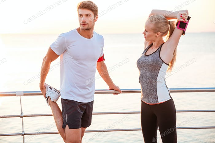 Athletic young couple stretching out after running