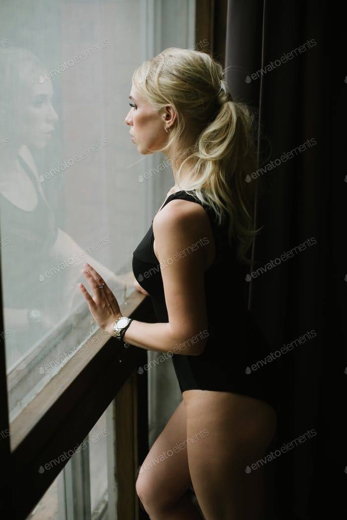 sporting beautiful girl near a window in a black bodysuit