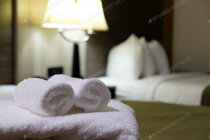 White bath towel on bed in hotel room