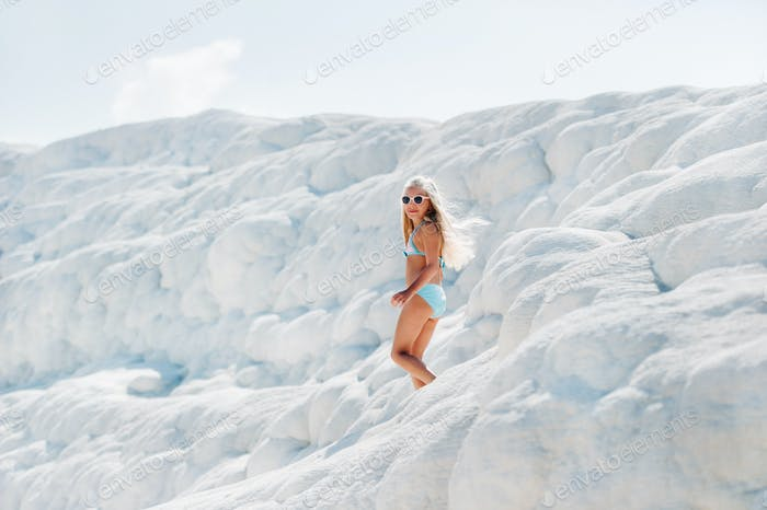 Girl in a swimsuit and sunglasses on White mountain, Sunny day, Pamukkale Turkey
