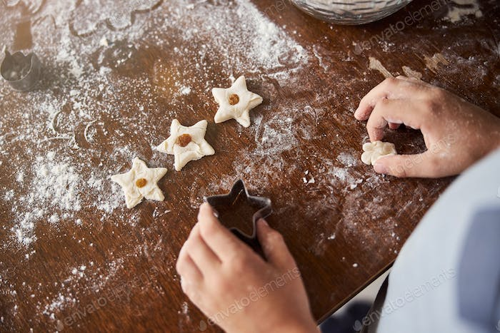 Enthusiastic chef making star-shaped cookies in the kitchen