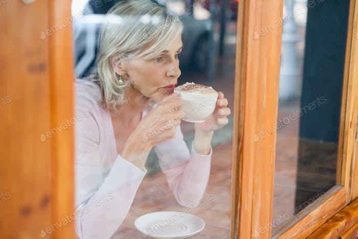 Nachdenkliche Senior Frau trinken Kaffee während sitzen am Tisch