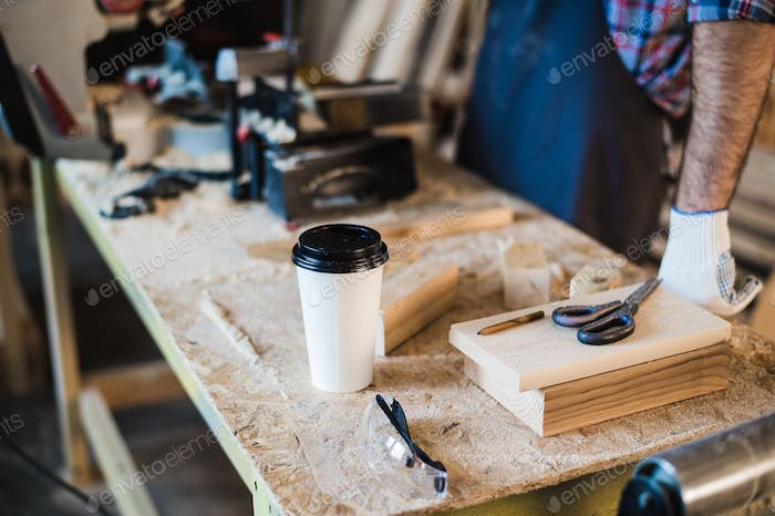 Modern carpentry work place with tablet, coffee, scissors and wooden pieces on table, in workshop