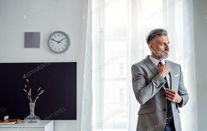 Ein ernster reifer Geschäftsmann, der in einem Büro steht.
