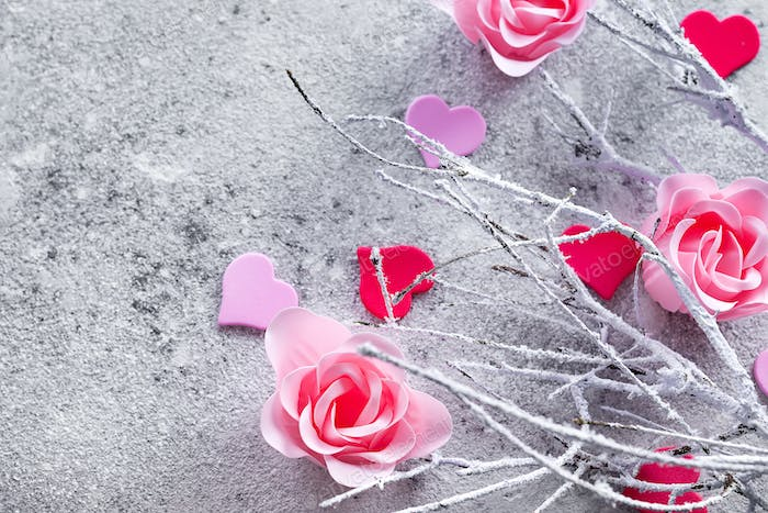 Branches in the snow with pink rose buds and hearts on a concrete background with space for text