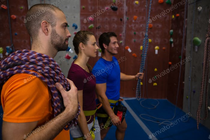 Trainer assisting athletes in wall climbing at club