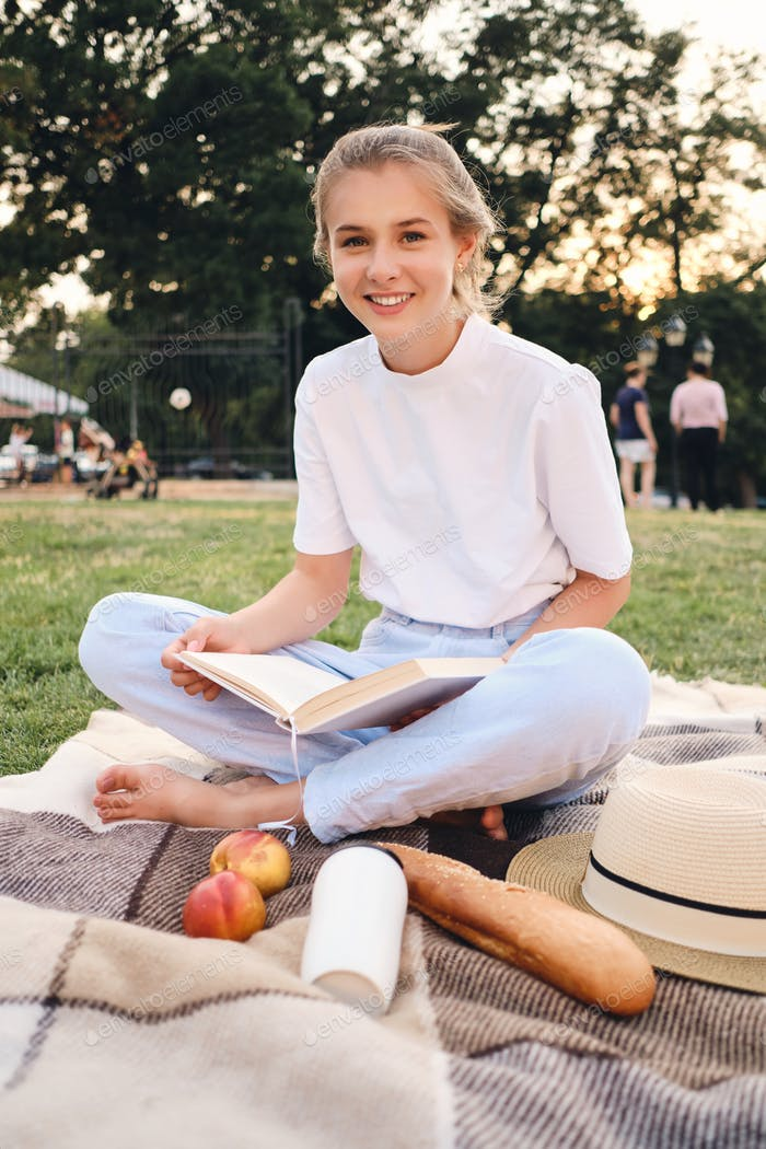 Young beautiful smiling woman sitting on plaid with book happily looking in camera on picnic in park