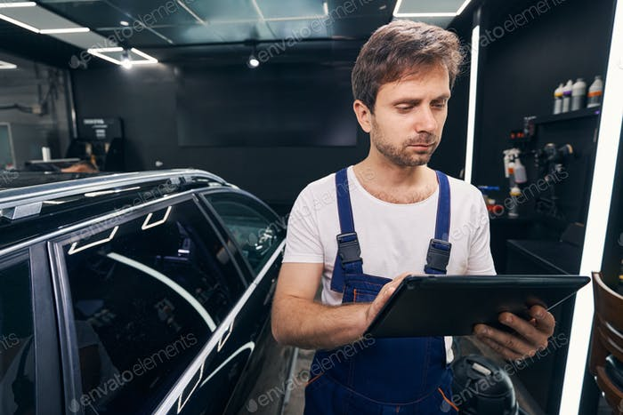 Auto repairman is checking information on tablet