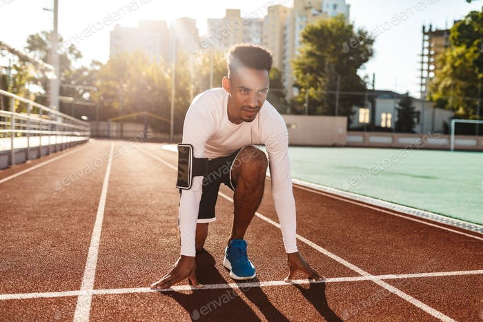 Young confident African American sportsman preparing for running on racetrack at city stadium