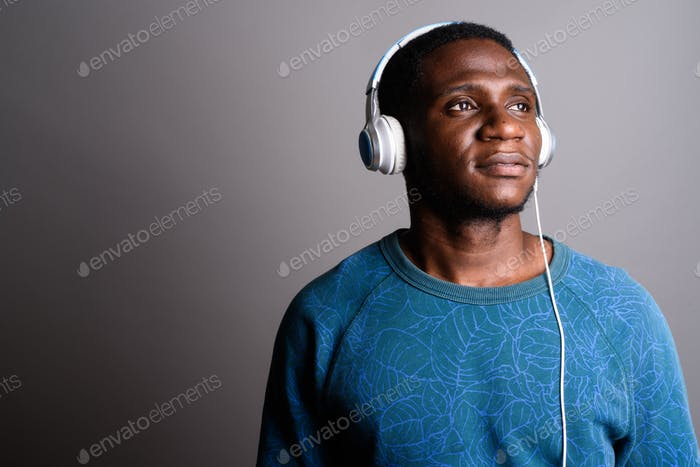 Young African man listening to music against gray background