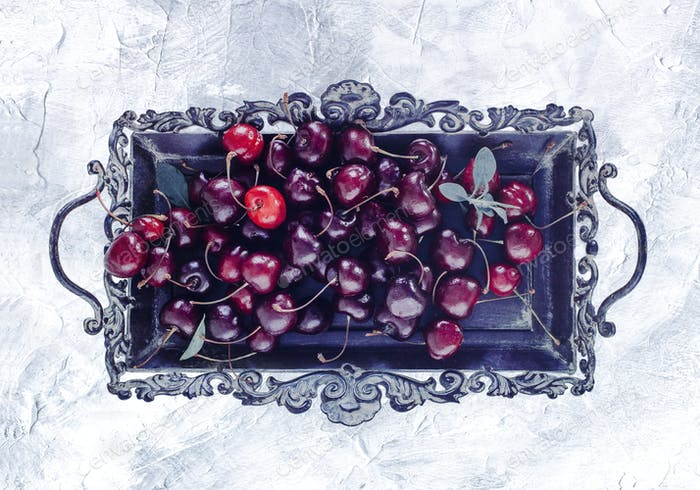 cherry on a metal vintage tray, white stucco