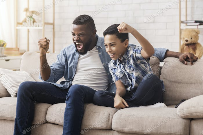 Afro Dad And Son Watching Sports On Tv And Emotionally Cheering