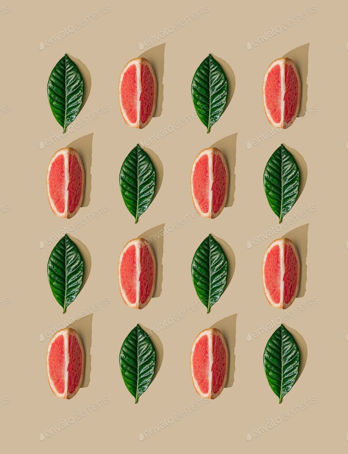 Minimal nature pattern with green leaves and grapefruit slices on pastel sand background.