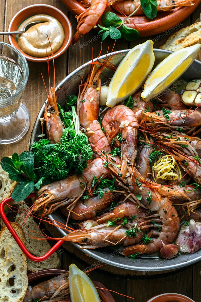 Roasted prawns shrimps in a pan with lemons, bread and wive