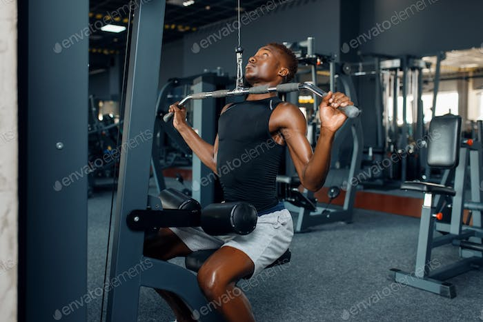 Muscular man in sportswear at exercise machine