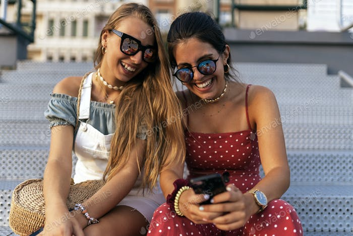 Cheerful women sitting on street and using cellphone