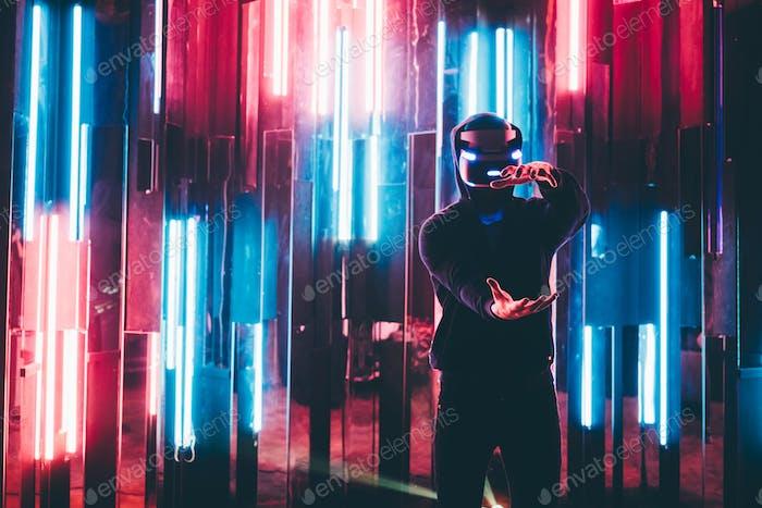 Portrait of man using VR headset in dark interior illuminated neon light.
