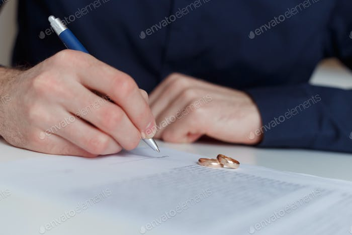 Alone husband signing divorce agreement.