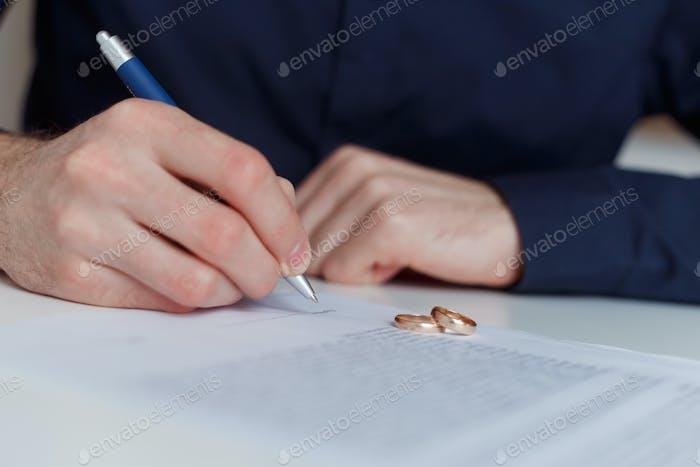 Marido solitario firmando un acuerdo de divorcio.