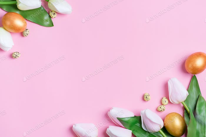 Corner festive frame from handmade golden painted eggs and fresh flowers on a pink background