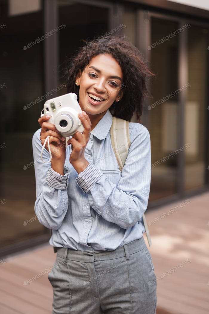 Portrait of young beautiful lady with dark curly hair standing with little white camera in hands