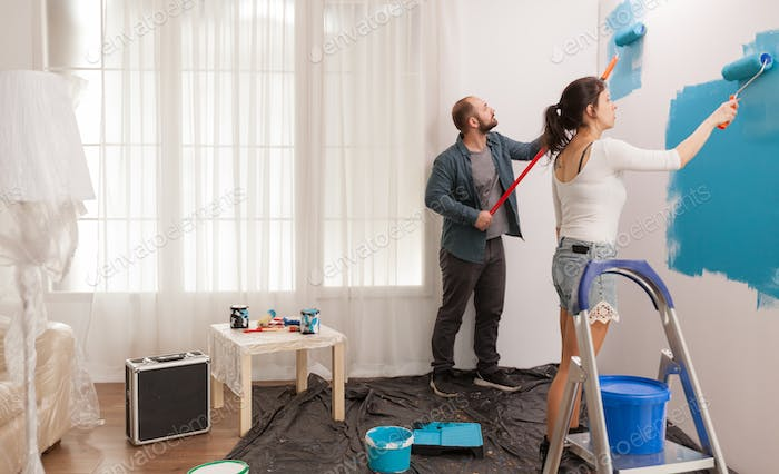 Husband and wife painting wall
