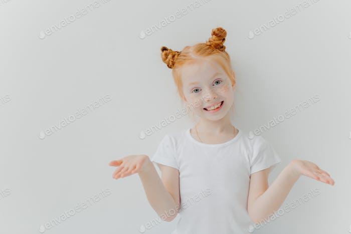Pretty small female kid with double foxy buns spreads palms sideways