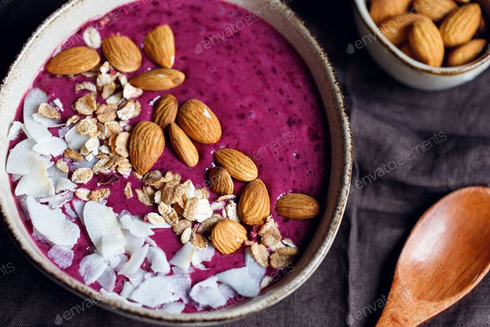 Purple berry smoothie with coconut flakes, oats and almond nuts.
