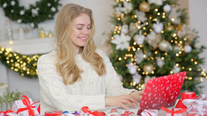Young pretty blond woman shopping online using laptop against Christmas background