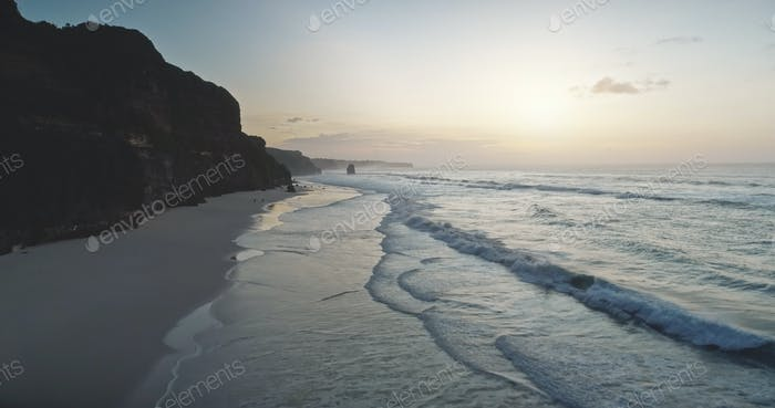 Sonnenaufgang an der welligen Luftaufnahme der Meeresklippen. Sonnenaufgang am dunklen Felsen, Meeresbucht Wasserwäsche Sandstrand