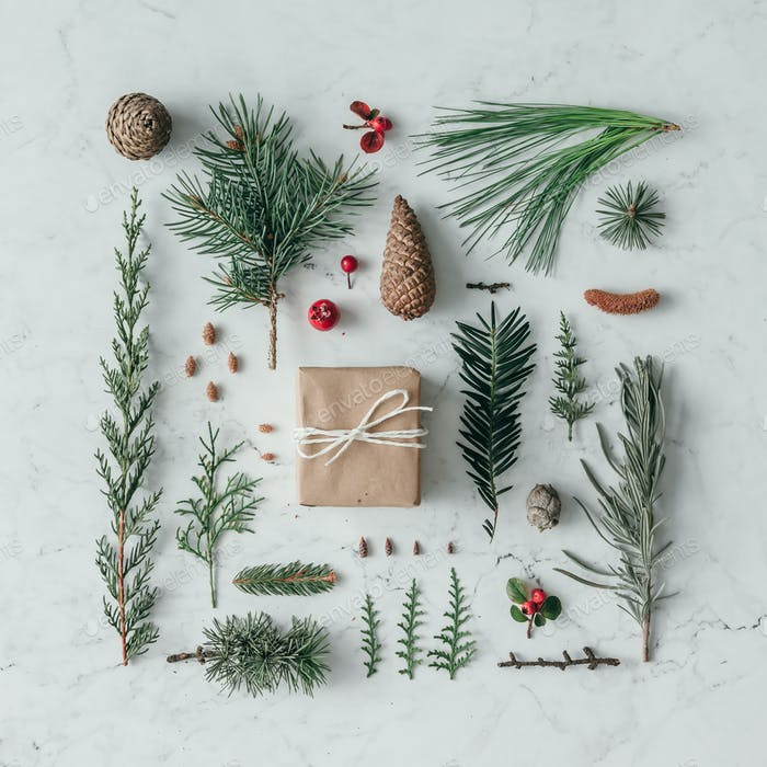 Creative natural layout made of winter things with christmas present on marble background.