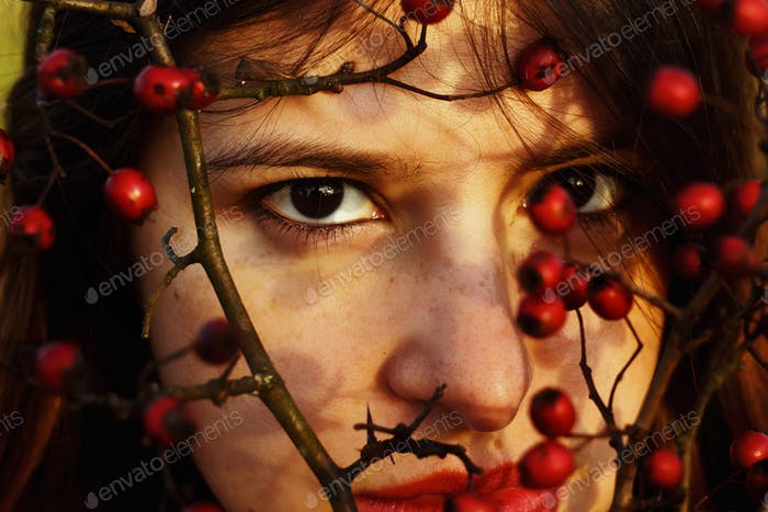 gorgeous stylish beautiful happy brunette girl and red berries of hawthorn