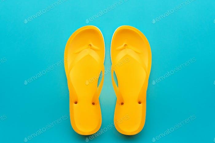 Yellow flip flops on blue background