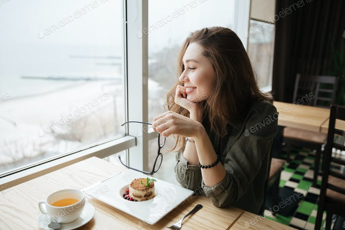Cheerful lady with long hair holding glasses sitting in cafe.