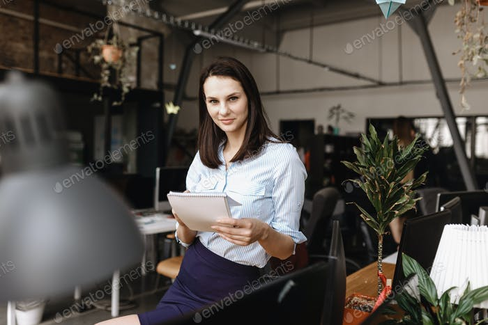 Young brunette girl dressed in office style clothes makes notes in a notebook standing in the modern