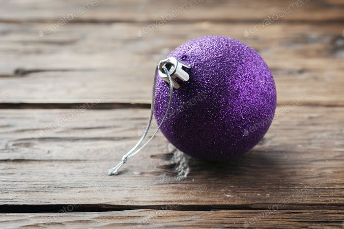 Christmas card with purple ball on the wooden table