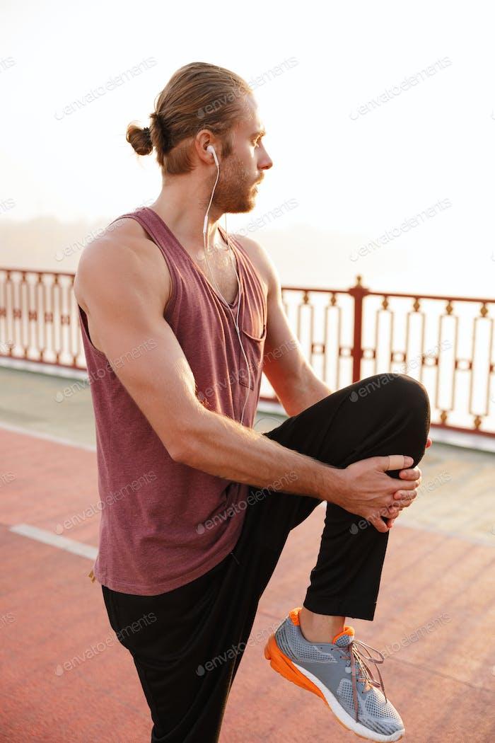 Attraktiver junger Fit-Sportler, der auf einer Brücke arbeitet
