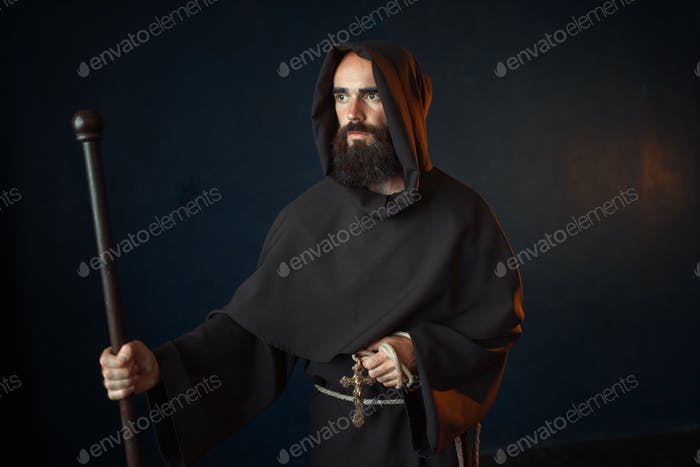 Medieval monk with wooden stick and cross in hands