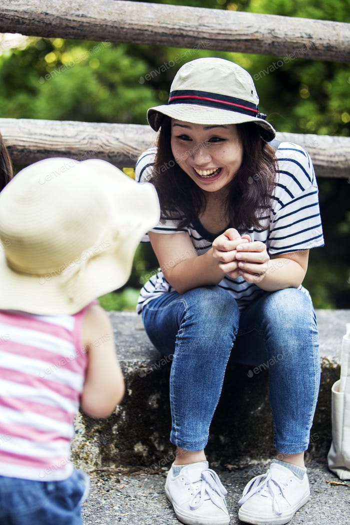 Smiling Japanese woman talking to little girl wearing sun hat, striped top and jeans.
