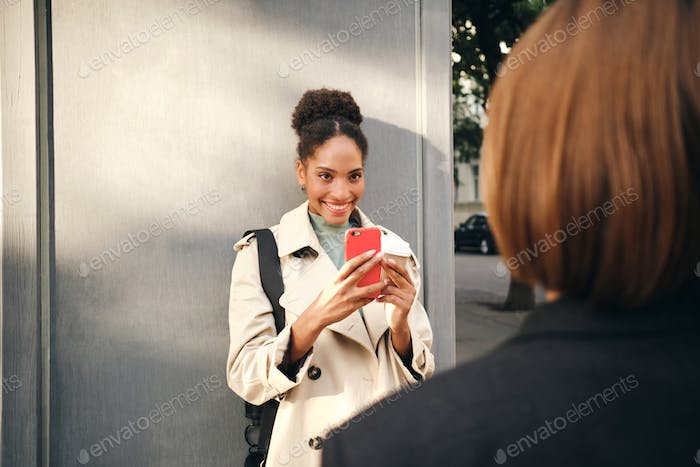 Smiling African American girl in stylish trench coat taking photo of her friend on cellphone outdoor