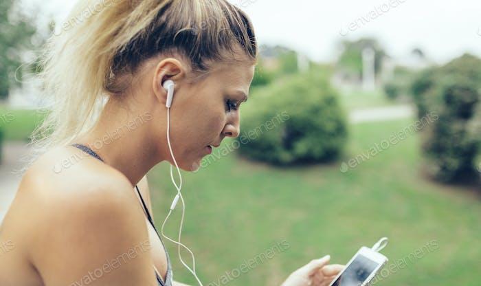 Женщина с наушниками, слушая музыку в смартфоне