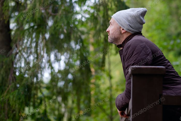 handsome mature man smiling in warm hat and jacket looking aside