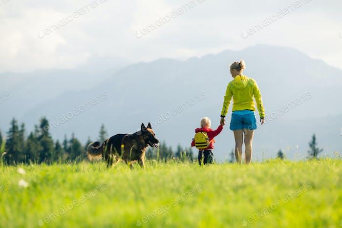 Alegre madre con Bebé niño paseando un perro