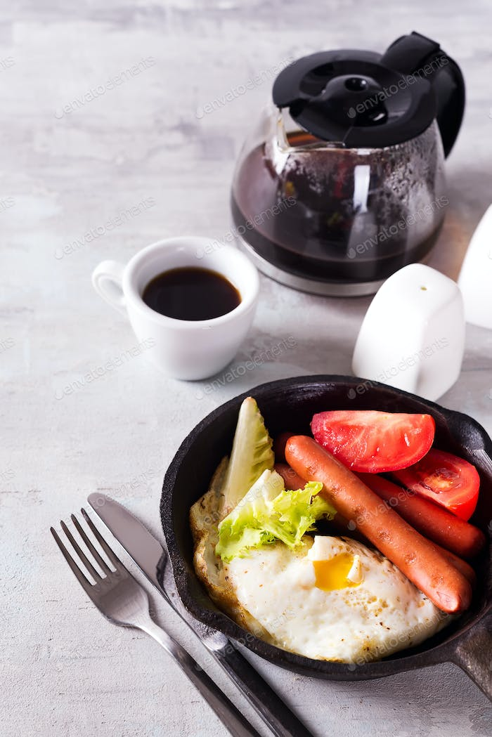 English breakfast in pan with fried eggs, sausages, toasts, vegetables and coffee on light stone