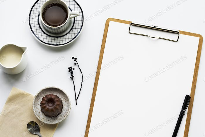 Aerial view of paper clip board and coffee cup